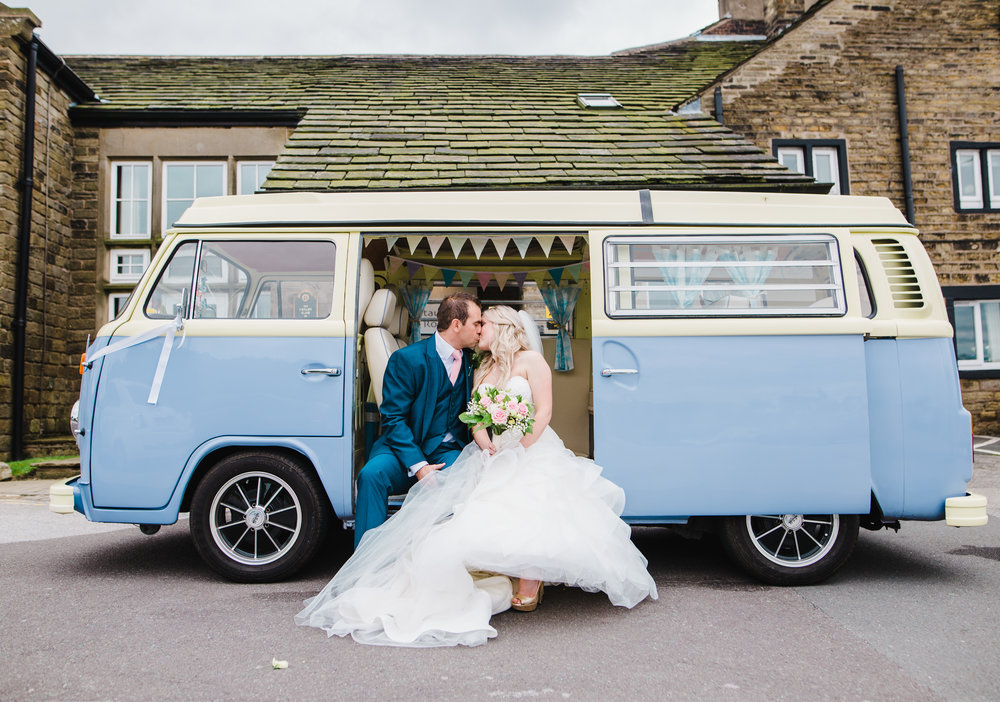 Creative photograph of the bride and groom sat in the camper van- Rustic themed wedding