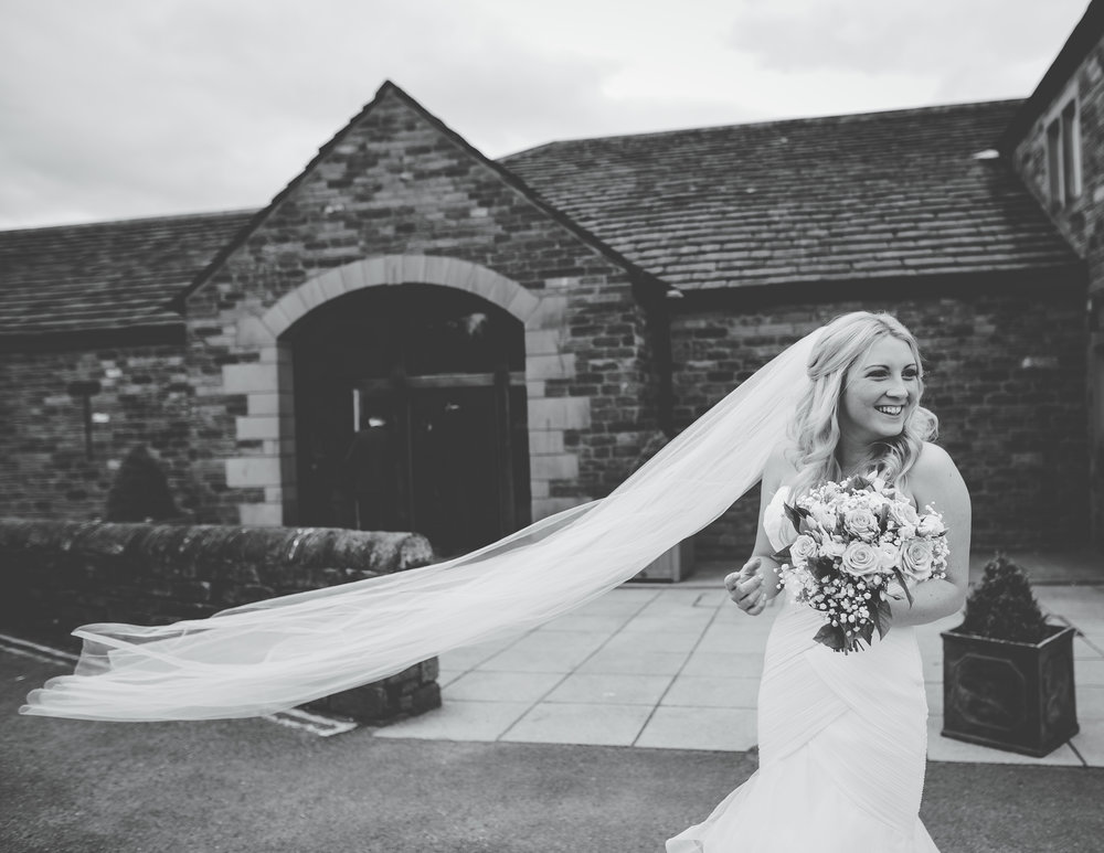 Black and white photograph of the bride outside The White Hart Inn at Lydgate