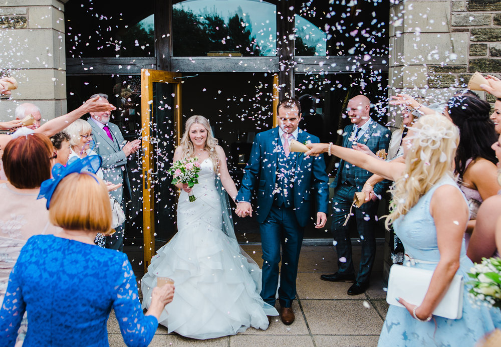 Bride and groom walking through confetti outside of The White Hart Inn at Lydgate