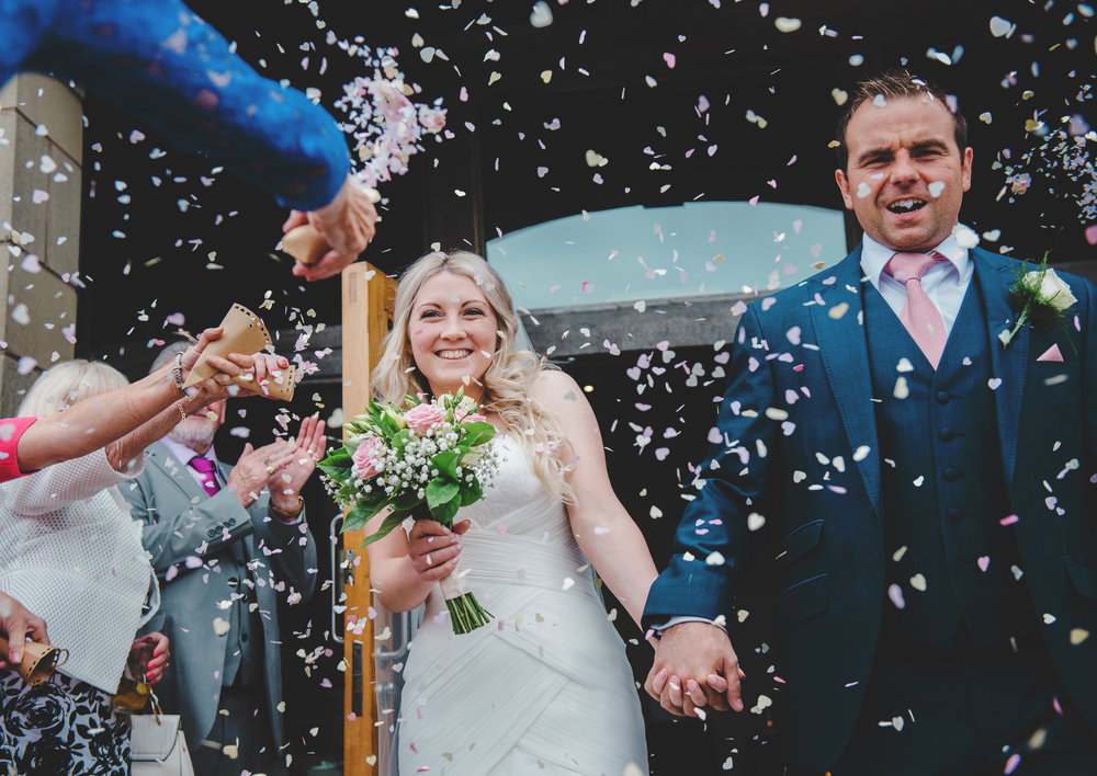 The bride and groom walking into helps of confetti - Documentary photography