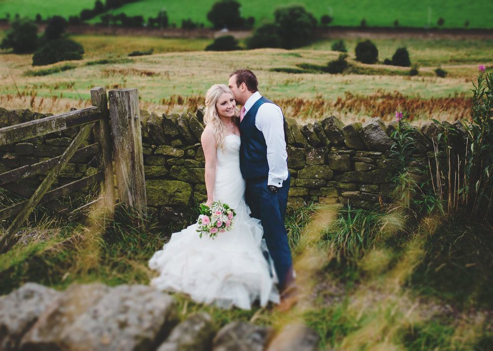 The bride and groom kissing in the distance- The White Hart Inn at Lydgate