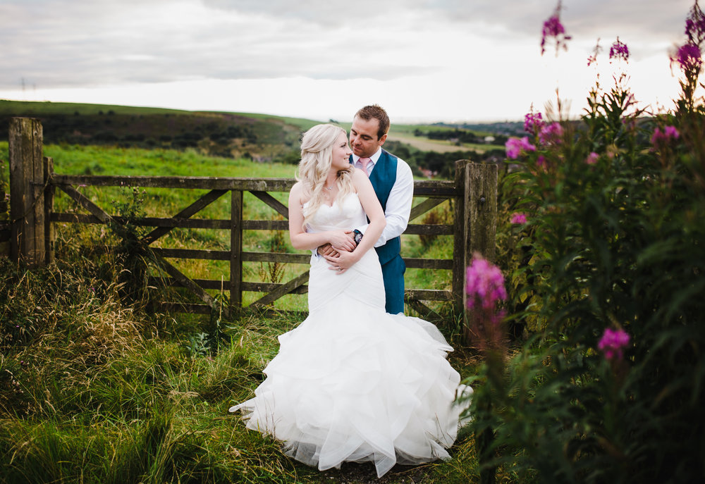 The bride and groom surrounded by the hills of manchester