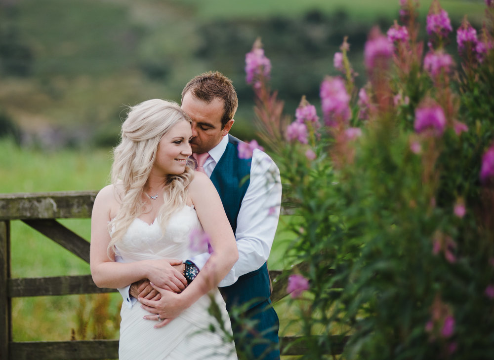The bride and groom hugging almonds the flowers at the manchester wedding venue The White Hart Inn at Lydgate