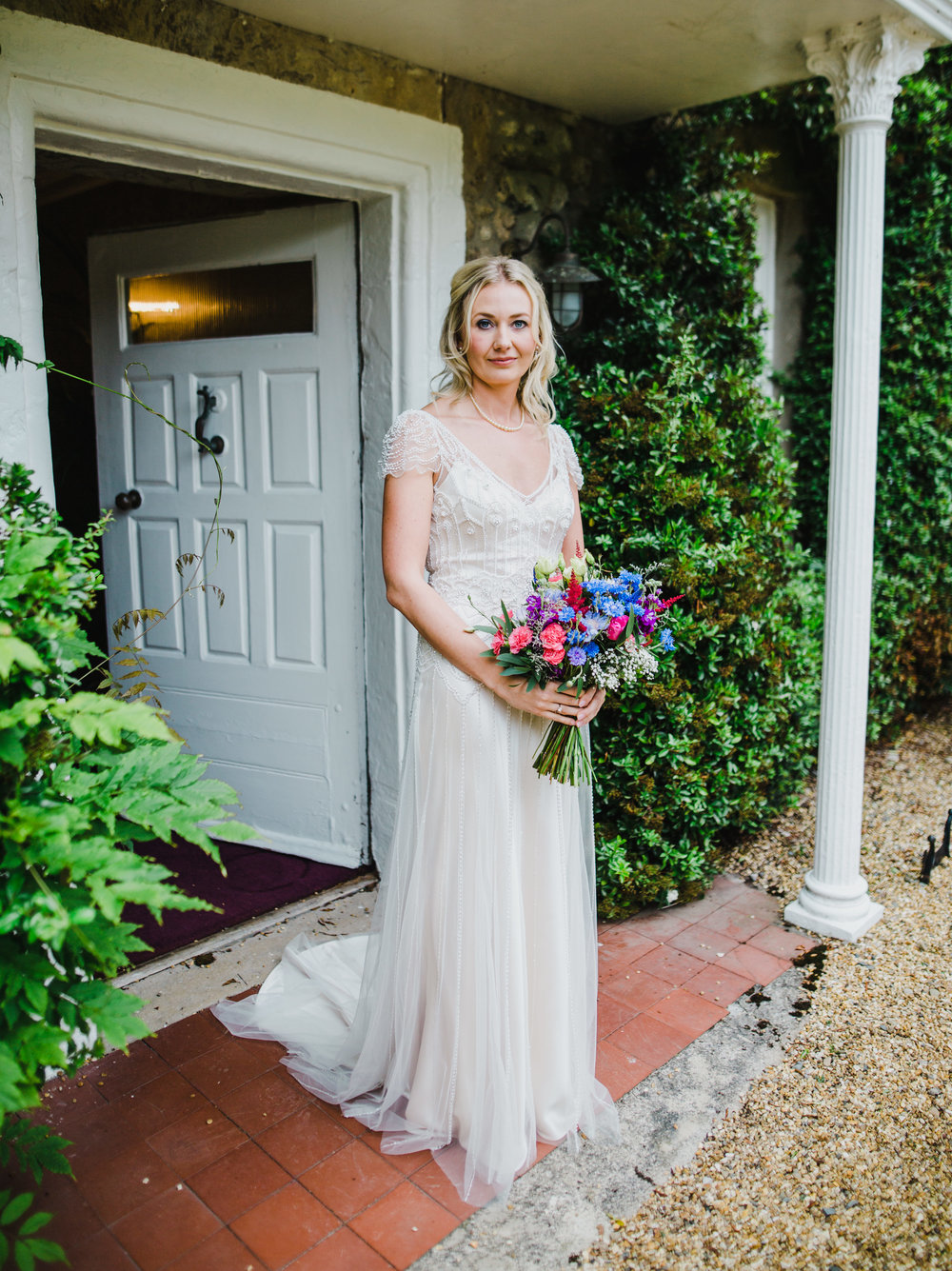 Portrait of the bride with her colourful flower bouquets.- hipping hall wedding