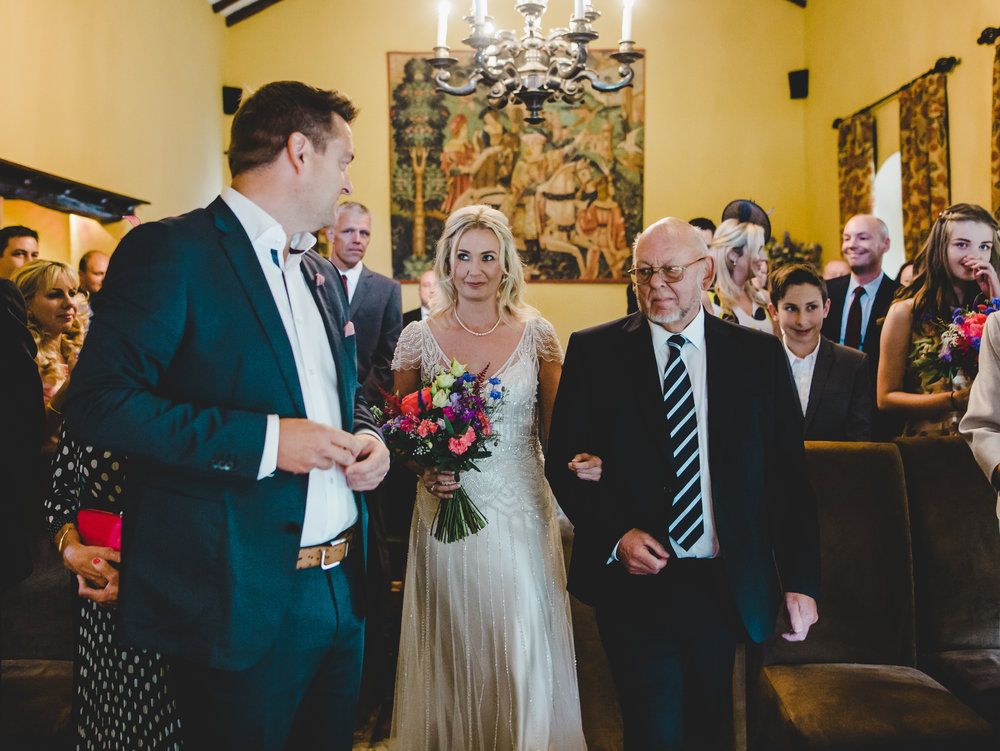 The groom looking back at his beautiful bride as she walks down the aisle.- Creative wedding photography
