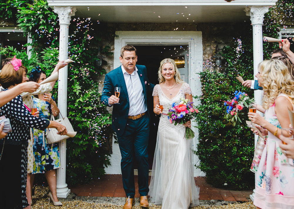 The bride and groom walking through confetti- Creative wedding photography