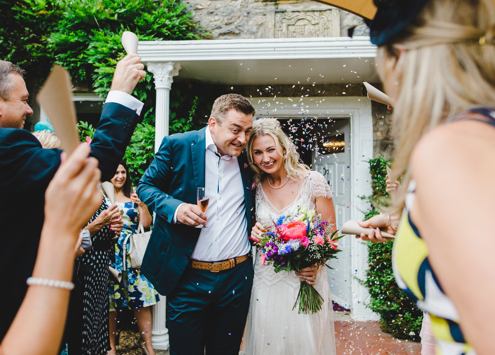 Groom and bride walking through air filled with confetti- Hipping Hall Kirkby Lonsdale