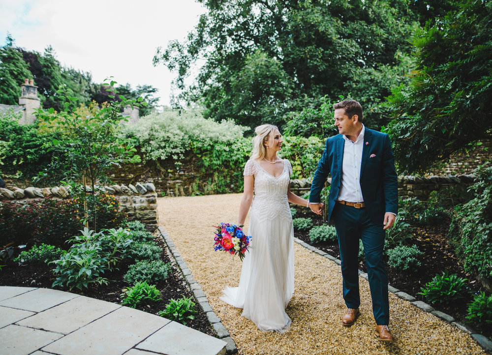 The bride and groom walking in the grounds of their wedding venue of Hipping Hall Kirkby Lonsdale