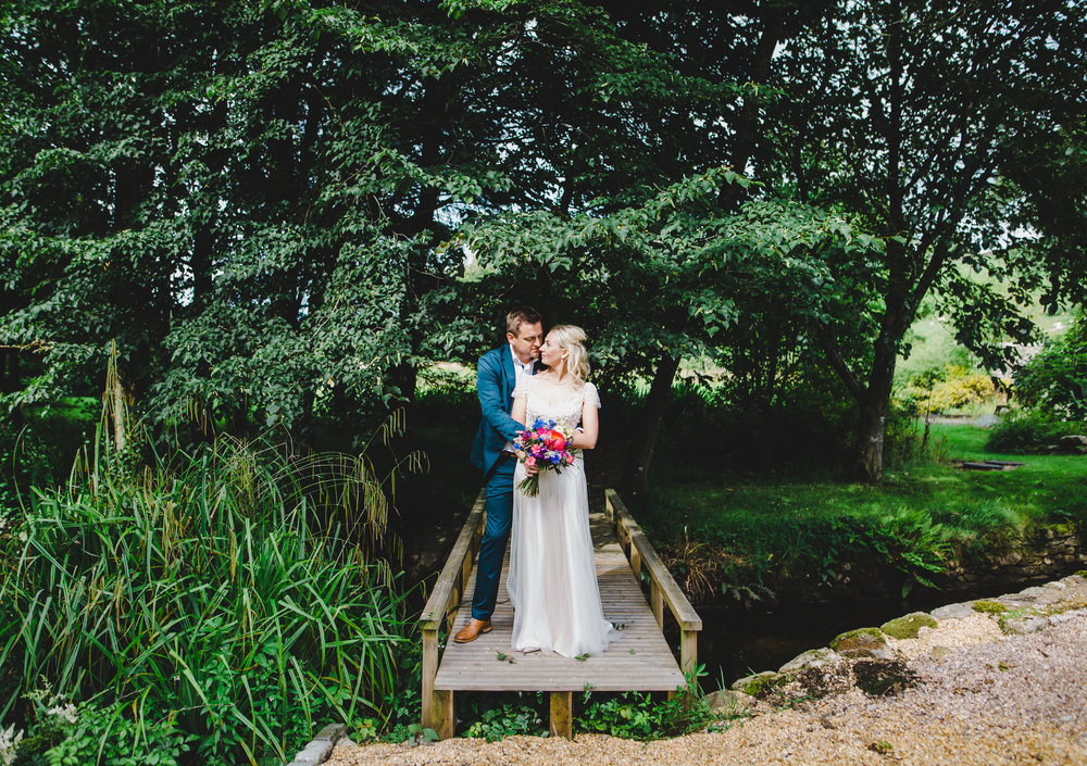 The bride and groom stood on a bridge at Hipping Hall Kirkby Lonsdale