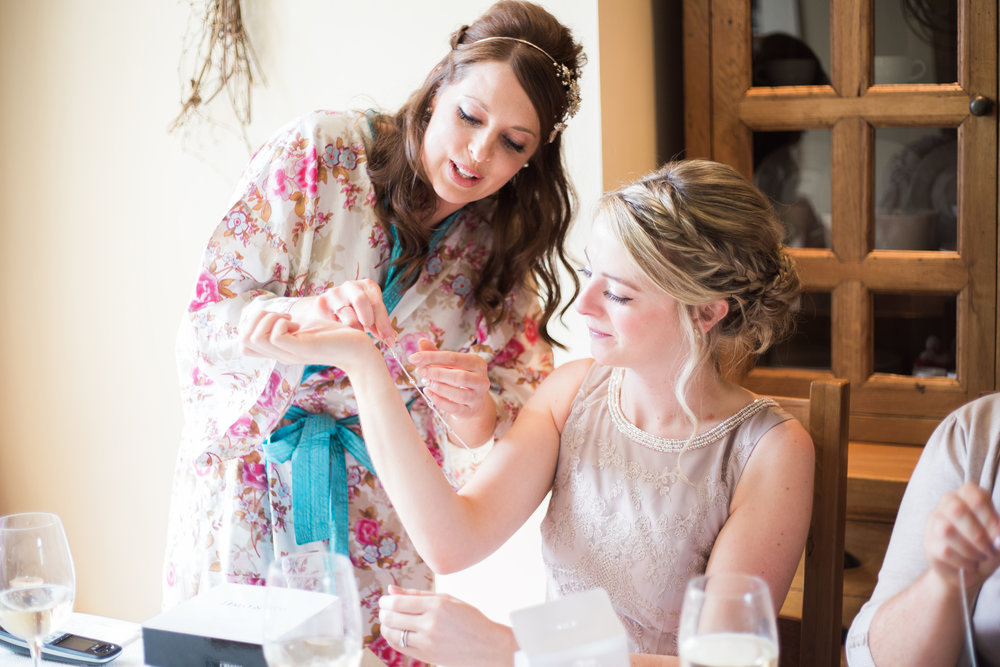 The bride helping the bridesmaid add the finishing touches- Lancashire wedding photography