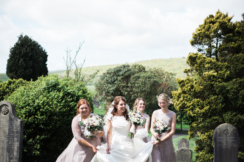 The bride and her bridesmaids on the windy day of her wedding- Hipping Hall wedding venue