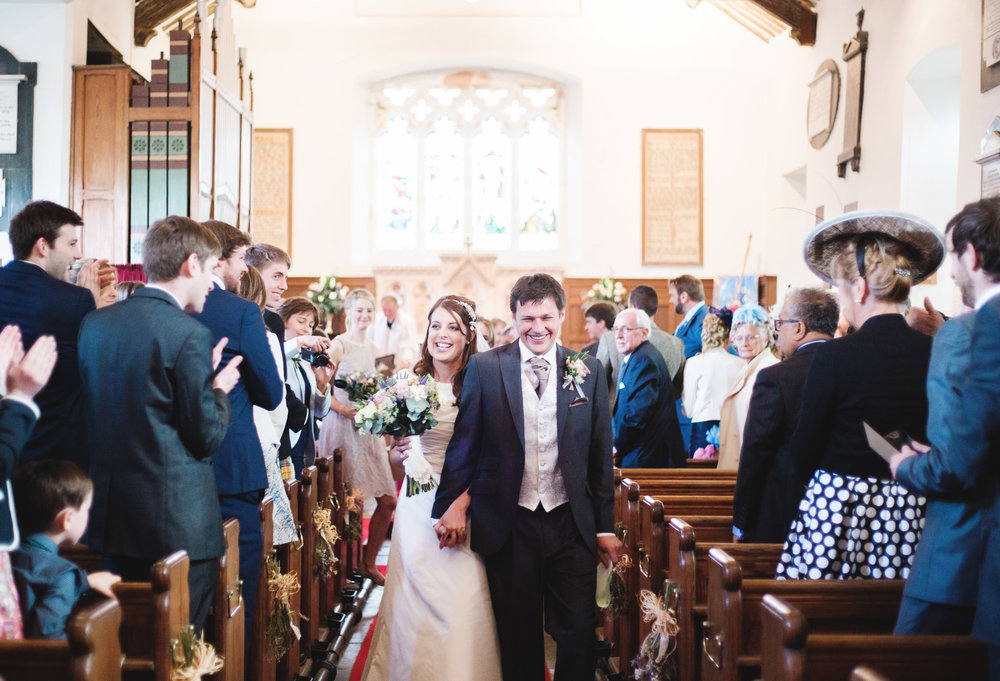 The bride and groom walking down the aisle- Documentary wedding photography