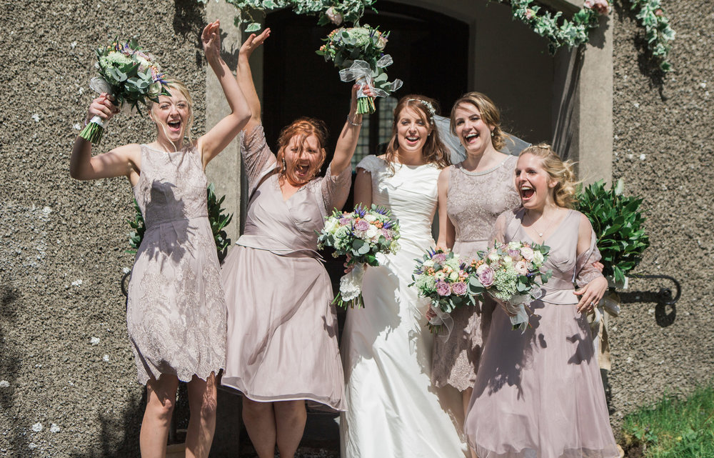 The cheerful bride and bridesmaid outside of Hipping Hall, Lake district