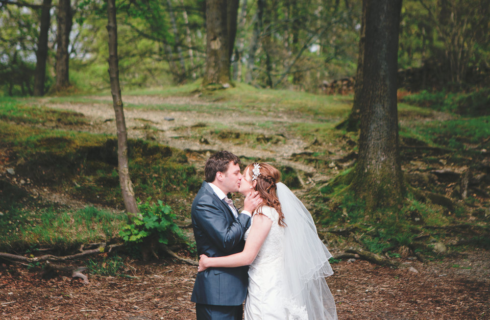 The bride and groom kissing surrounded by the greenery at Hipping Hall