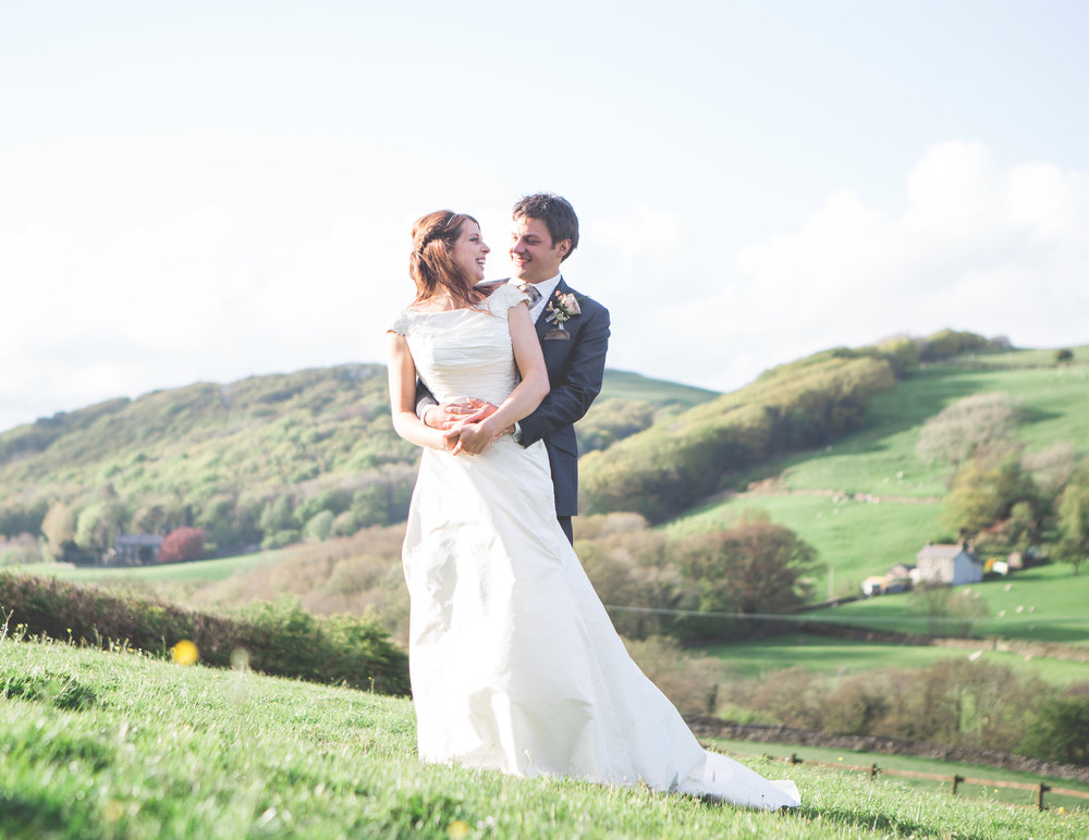 The bride and groom surrounded by the hills of the lake district
