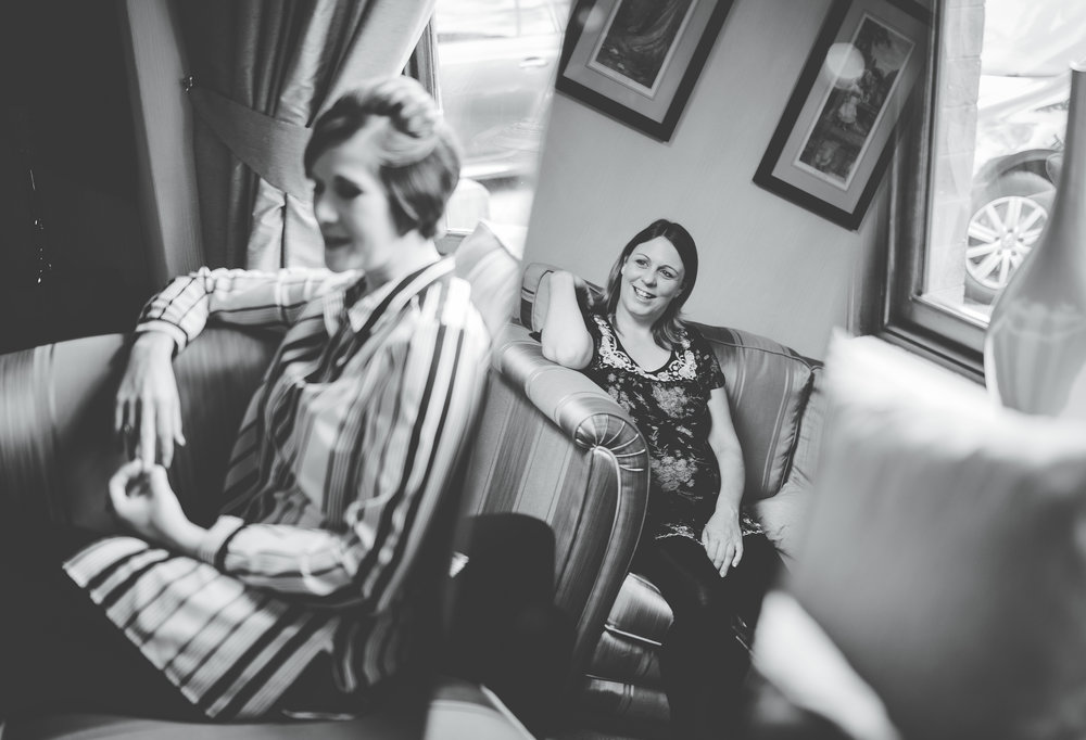 Black and white photograph of two the wedding guest as they watch the bride get her makeup done- Lancashire wedding photography