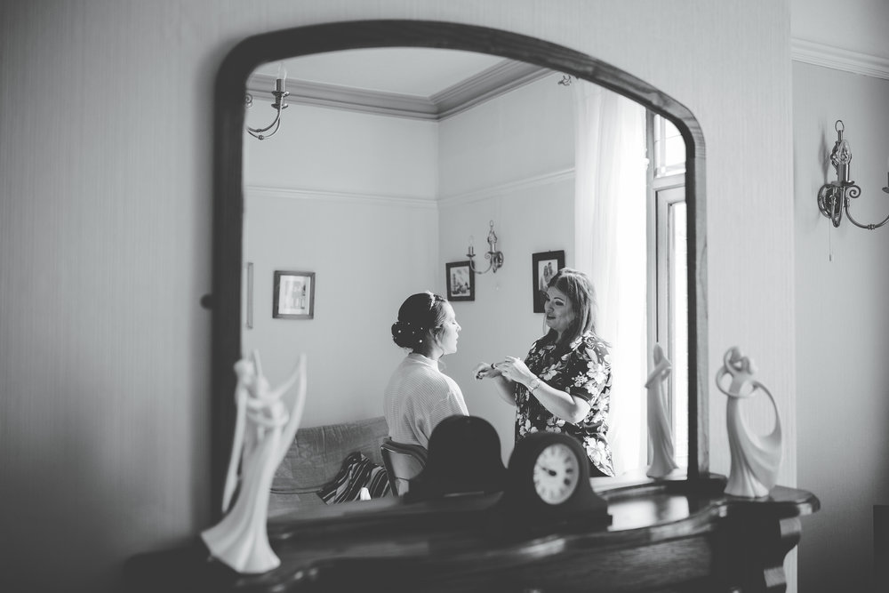 Through the mirror photograph of the bride getting her makeup done- Relaxed wedding photography