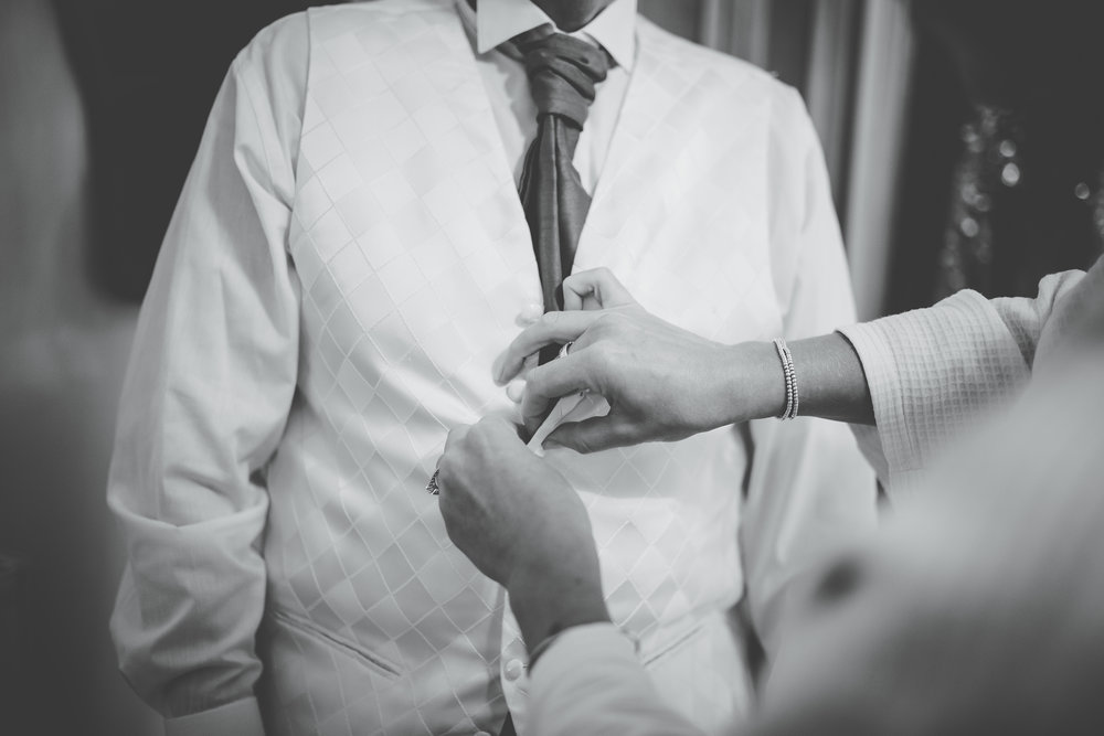 Black and white photograph of the groom fastening up his waist coat