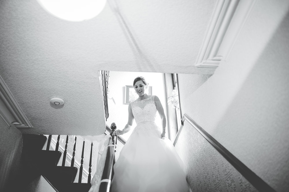 Black and white photograph of the bride walking down the stairs- Documentary wedding photography, Lancashire