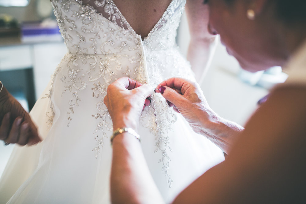 The bride getting her dress buttoned up- Calm relaxed wedding photography