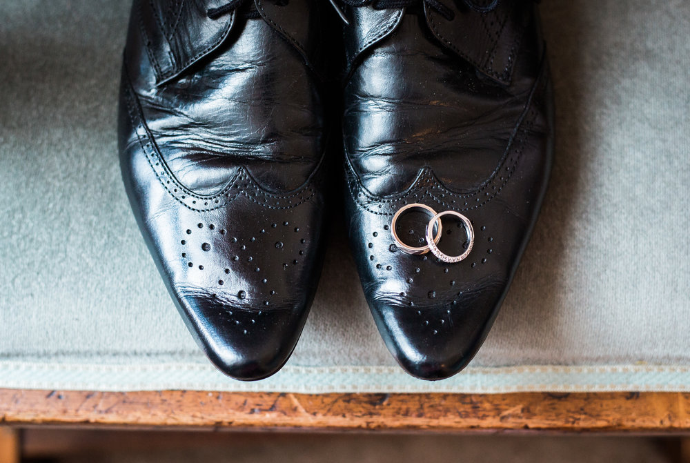 Creative wedding photograph of the wedding rings on the grooms shoes- Creative wedding photography
