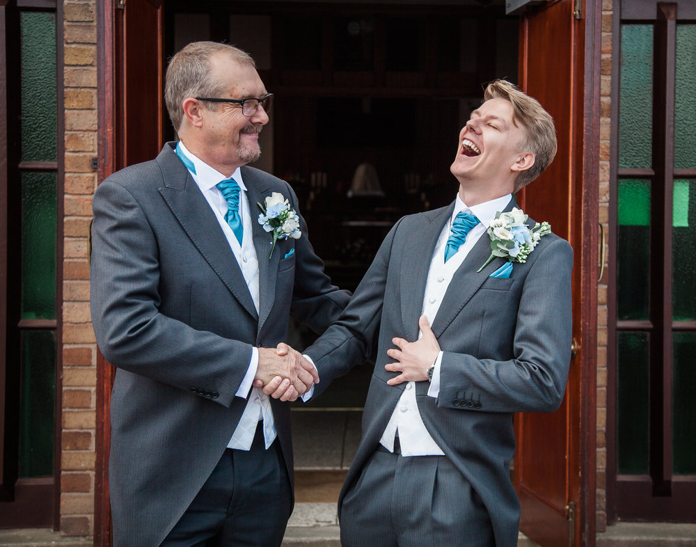 The groom with a wedding guest laughing and shaking hands- Documentary wedding photography