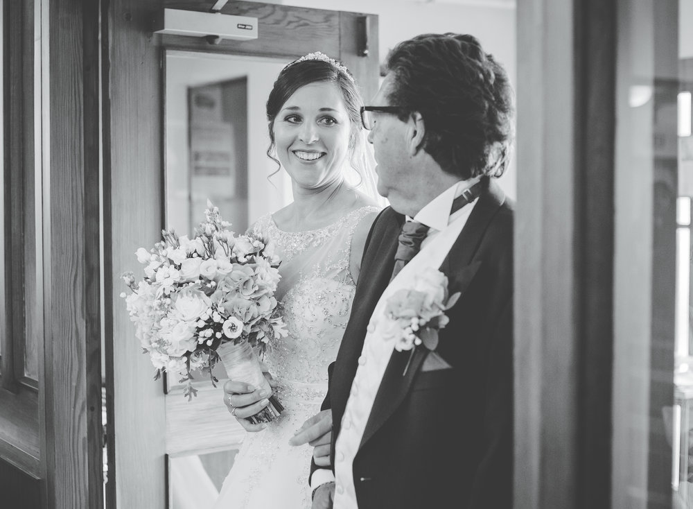 The bride walking down the aisle with her father- modern wedding photography