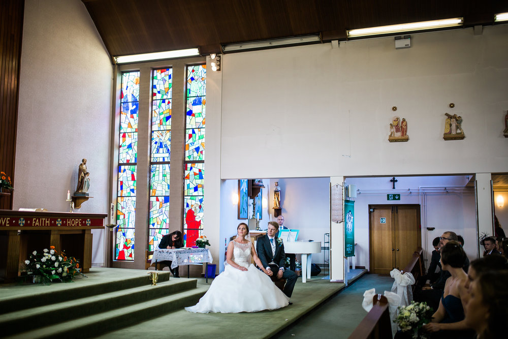 The bride and groom sat waiting in the church- relaxed wedding ceremony