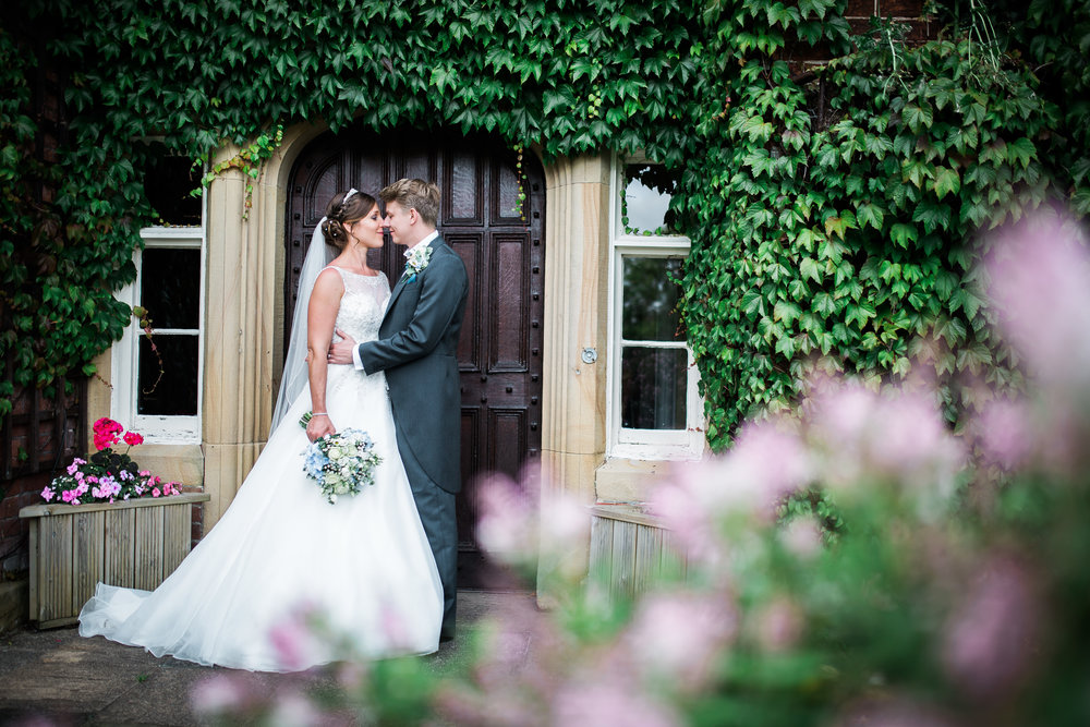 creative wedding photograph of the bride and groom in the doorway of The Villa at Wrea Green