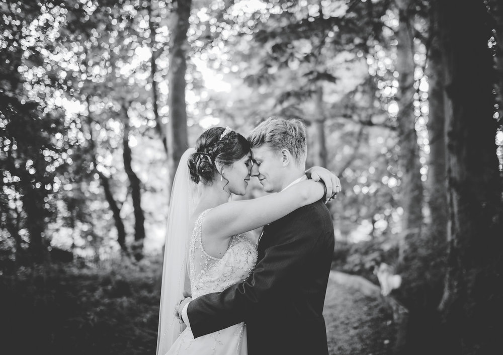 Black and white photograph of the bride and groom surrounded by trees outside of The Villa at Wrea Green