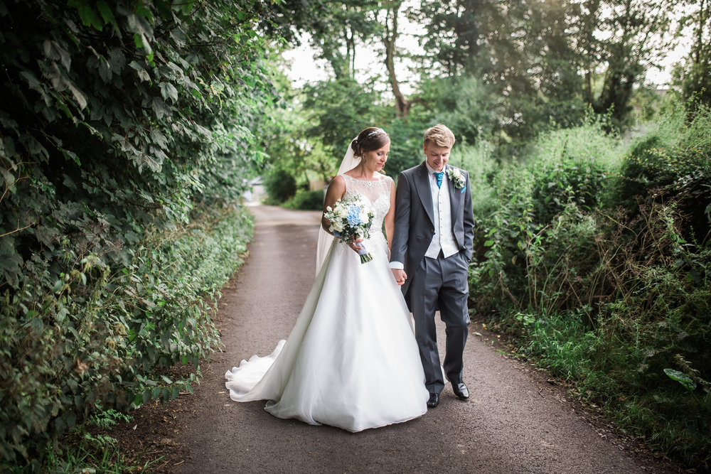 The bride and groom walking towards their wedding venue, The Villa at Wrea Green- Creative wedding images in lancashire