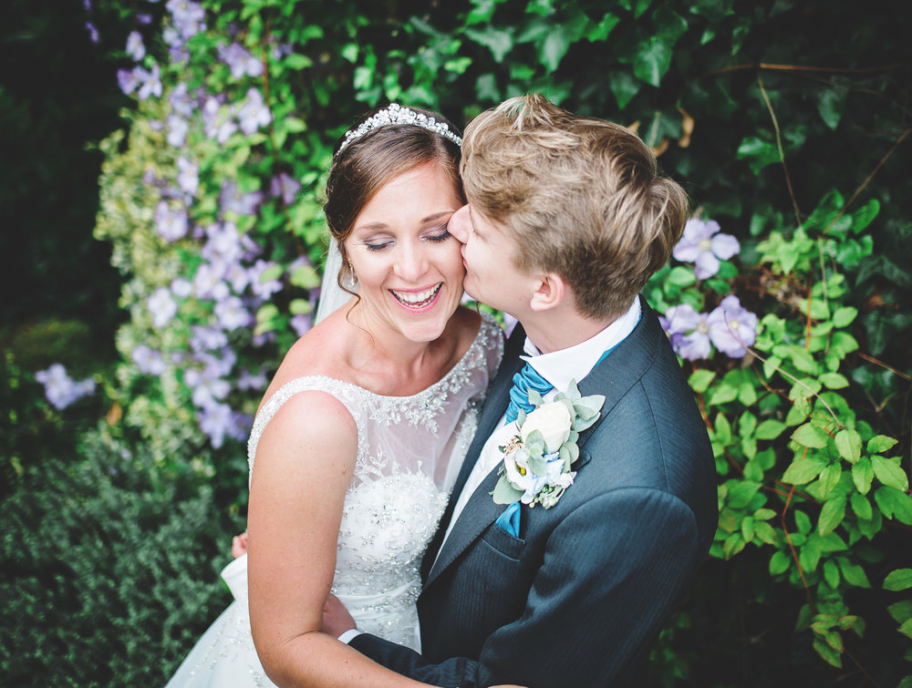 the groom kissing his bride in front of flower-relaxed photography, wedding