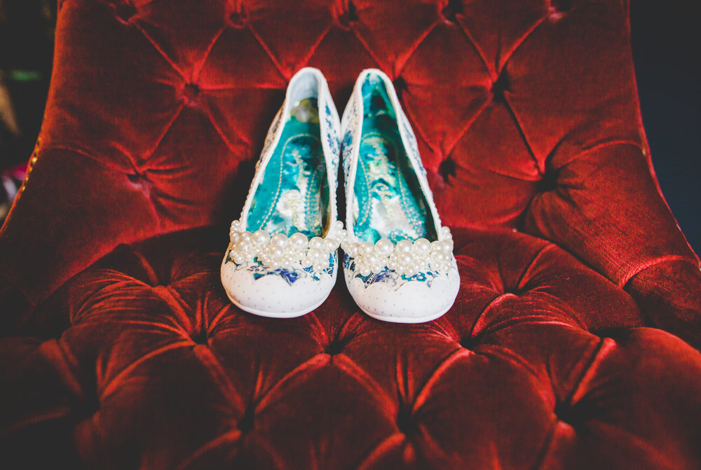 The brides wedding shoes on a red velvet chair- Bashall barn wedding