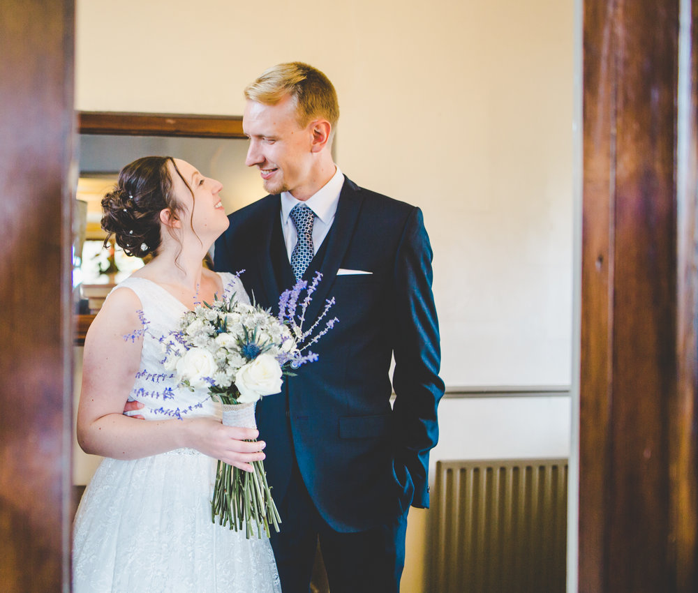 The bride and groom looking at one another- Bashall barn, rubble valley