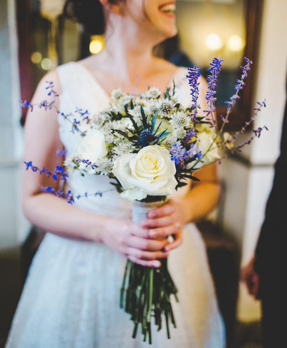 The bride holding her white and purple flower bouquet- Lancashire wedding photography
