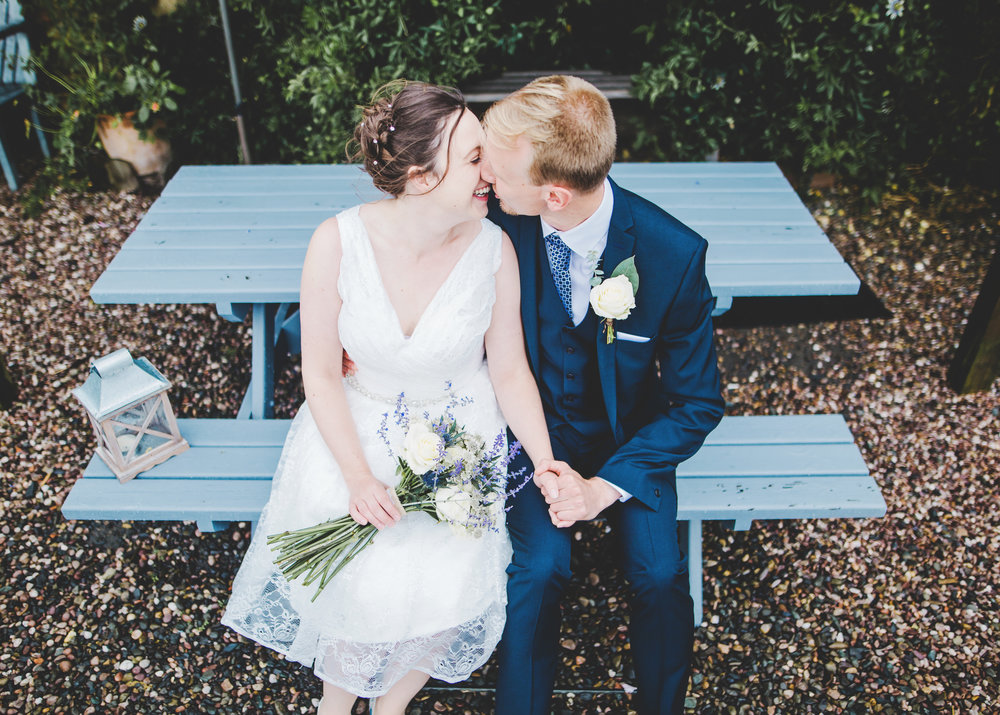 The bride and groom kissing on a blue bench- Relaxed wedding photographer