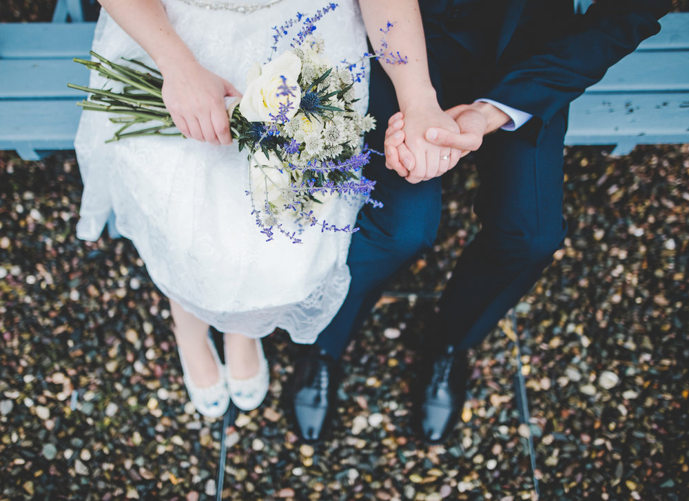 Creative photograph of the bride and groom sat on a bench