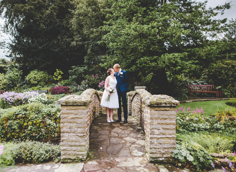 The bride and groom on a bridge kissing- Creative wedding photography, ribble valley