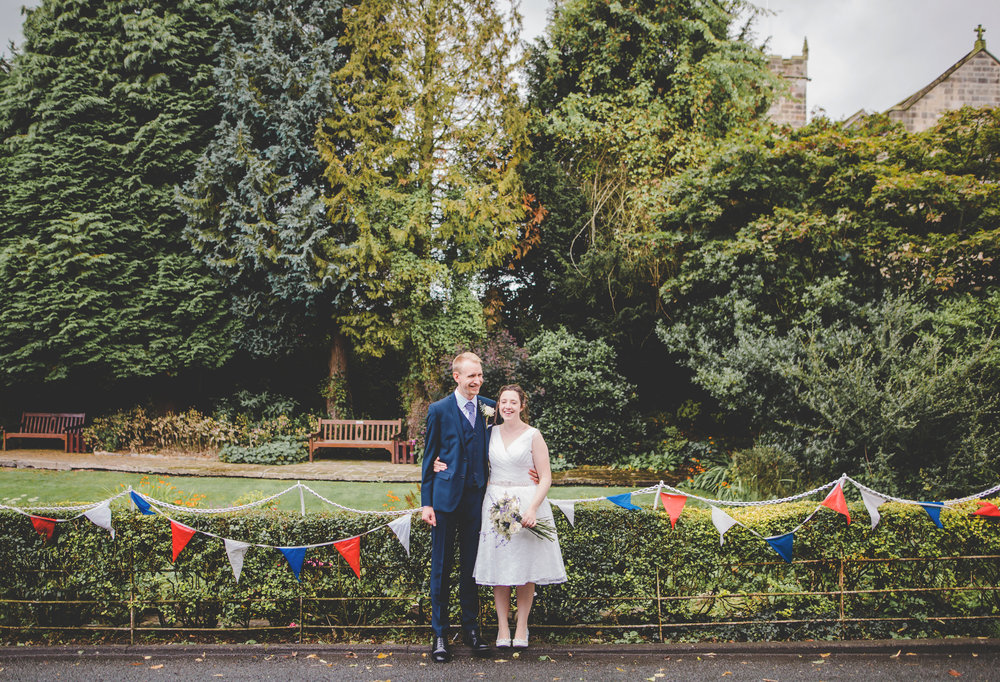 The bride and groom stood infant of flowers at Bashall barn wedding venue