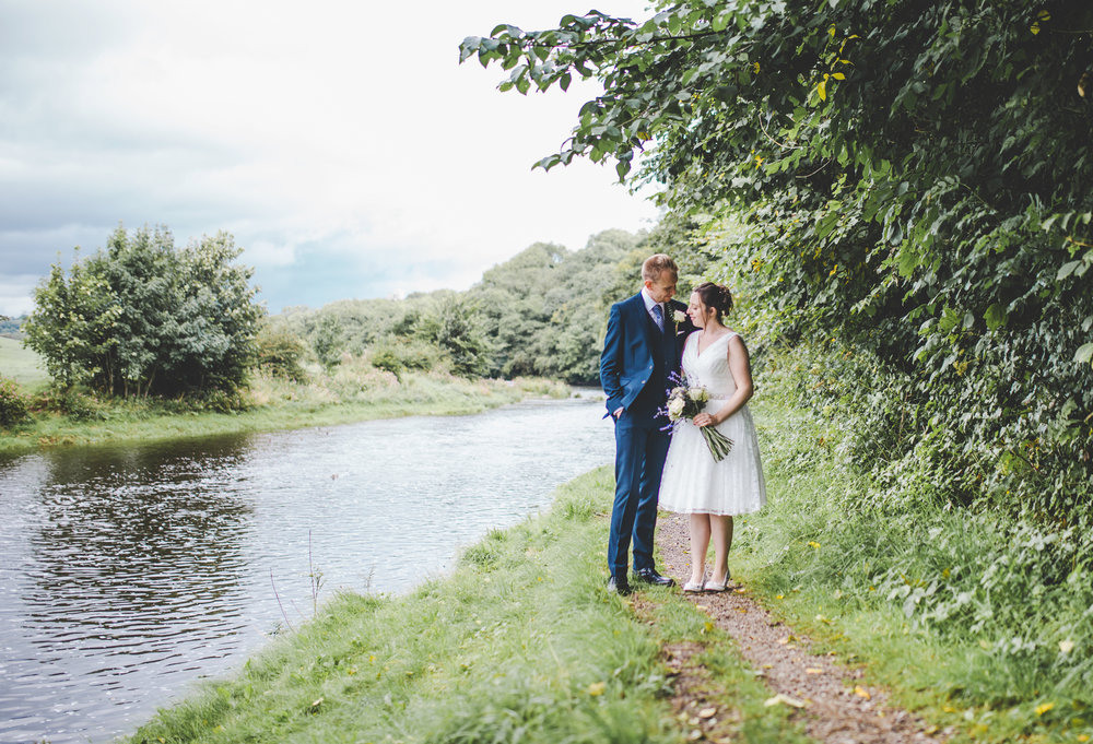 The bride and groom surrounded by the river- Ribble valley, Bashall barn wedding