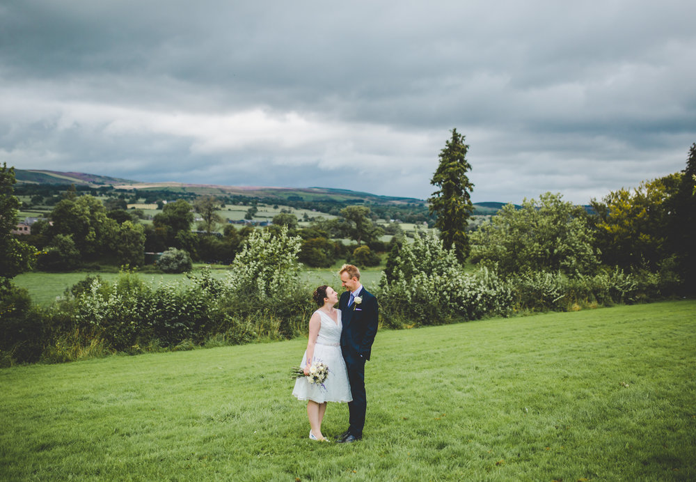 Bride and groom surrounded by the grounds of the Bashall barn.