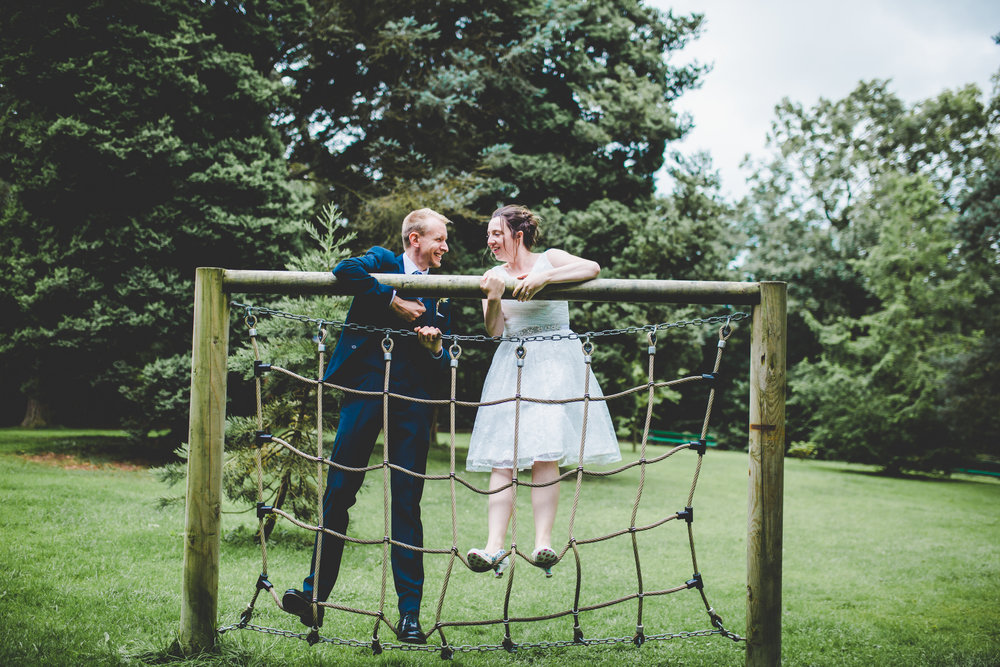 bride and groom playing on the climbing rope at Bashall barn in rubble valley