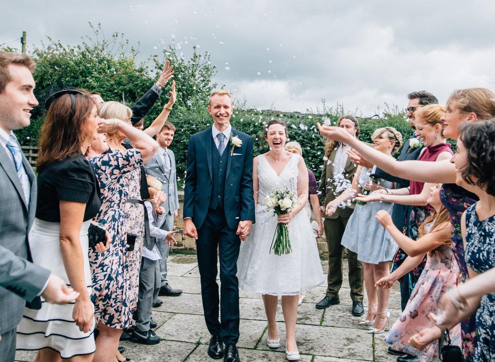 The bride and groom walking through confetti- Lancashire wedding photography