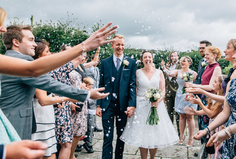 Bride and groom getting confetti thrown at them- rubble valley relaxed wedding photography