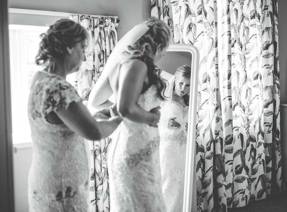 Black and white photograph of the bride getting into her wedding dress- relaxed wedding photography