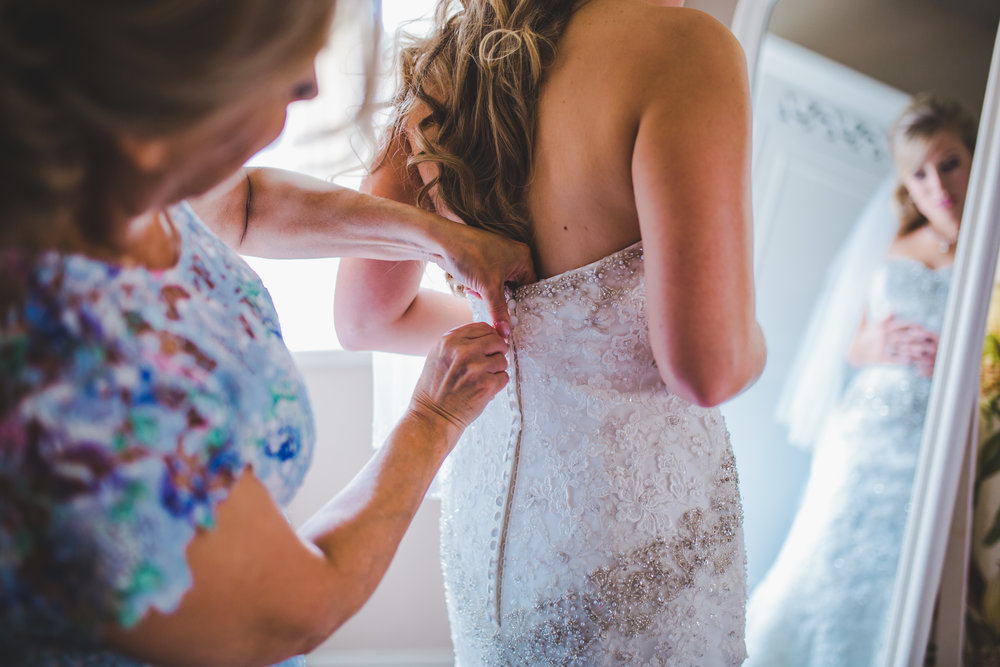 Mother of the bride doing up the brides wedding dress- Documentary photography