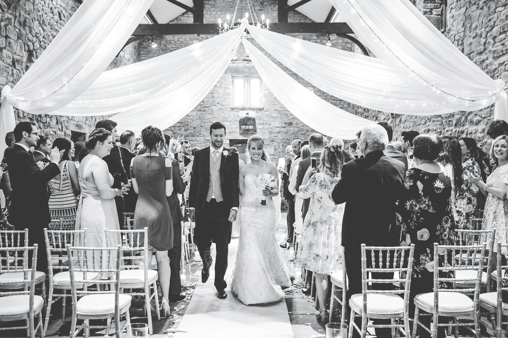 Black and white photography of the bride and groom walking down the aisle- Relaxed wedding photography