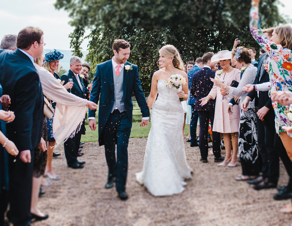 Bride and groom walking through confetti at Browsholme Hall