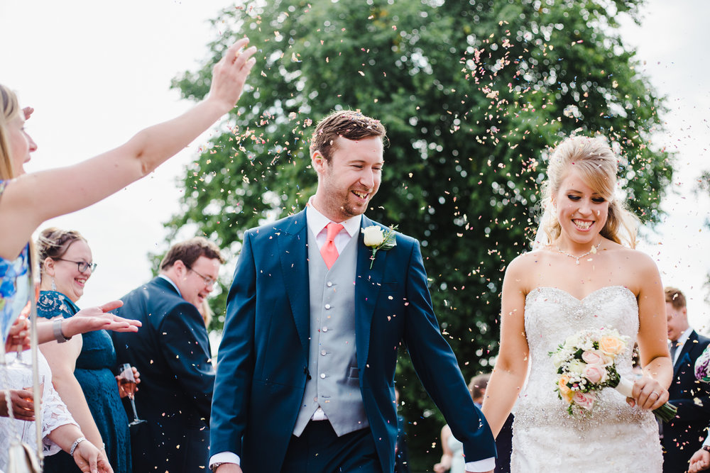 Bride and groom hand in hand through confetti- Browsholme Hall
