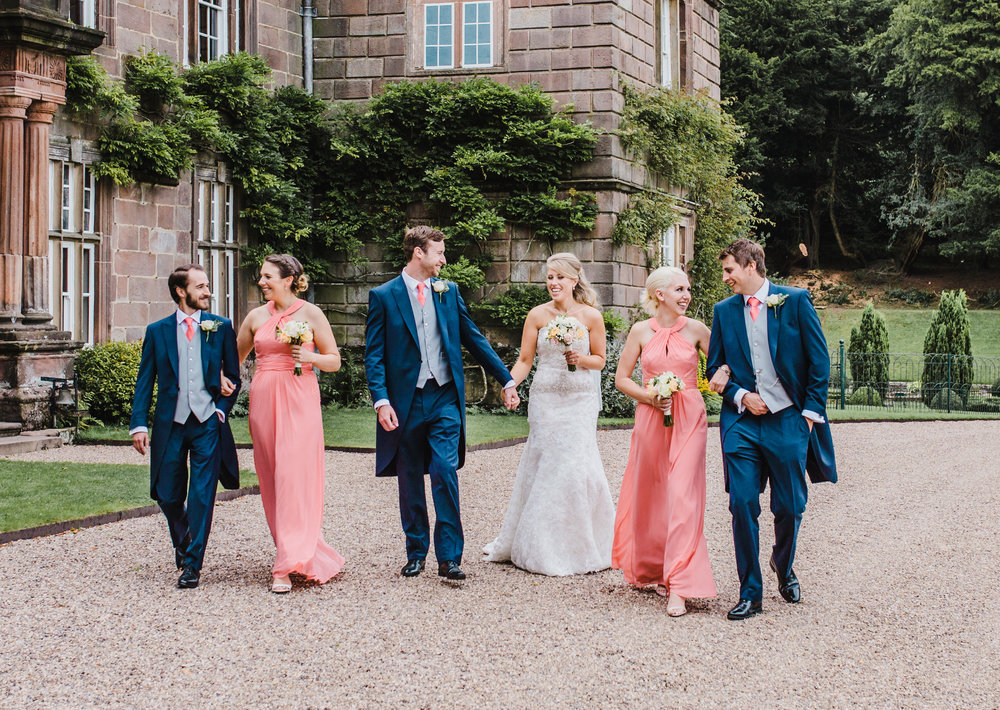Bride, bridesmaids, groom and groomsmen walking infant of Browsholme Hall- modern relaxed wedding